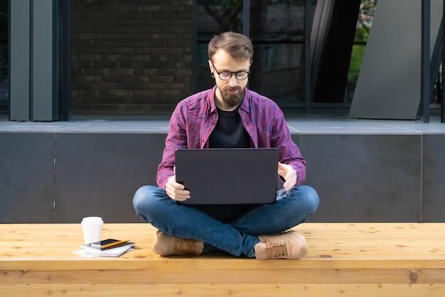 Uomo in vetri che si siedono a gambe accavallate sul banco di legno con il computer portatile