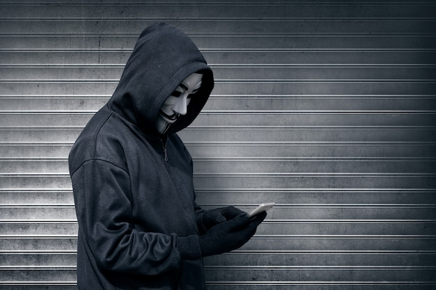 Uomo incappucciato con maschera di vendetta utilizzando il telefono cellulare