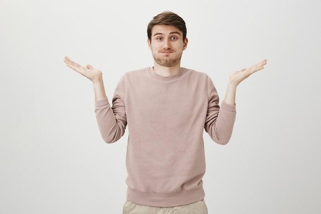 Uomo indeciso perplesso che fa il broncio e scrolla le spalle senza tracce
