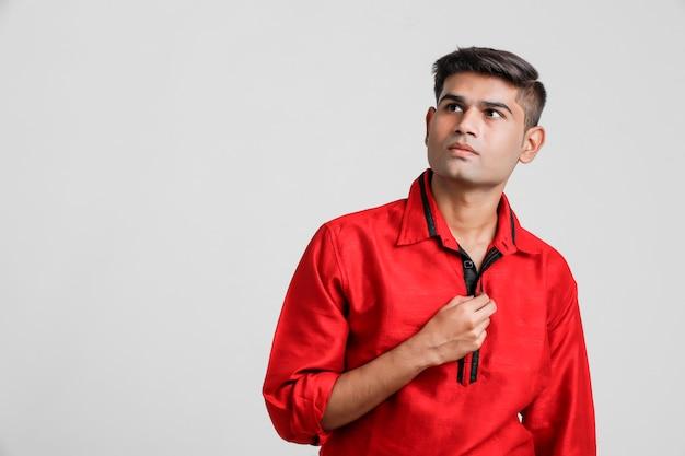 Uomo indiano / asiatico in camicia rossa e mostrando espressione multipla sopra bianco