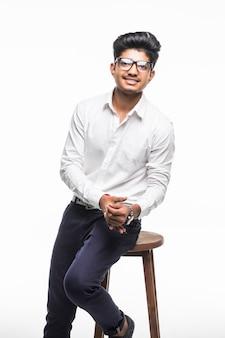 Uomo indiano bello bello che si siede su una sedia e che si rilassa, isolato per la parete bianca