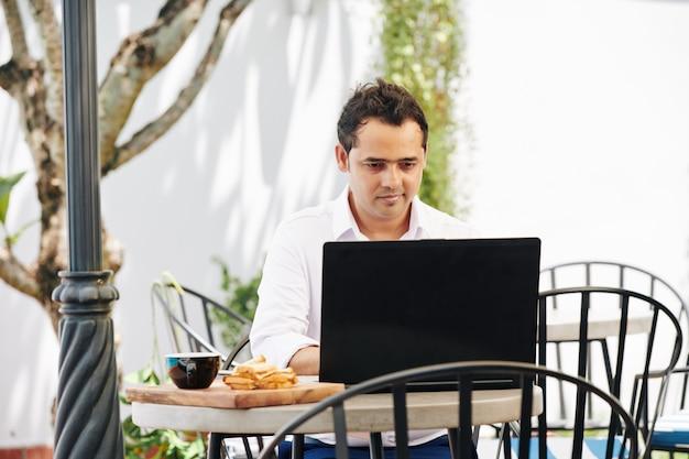 Uomo indiano che lavora al computer portatile in caffè