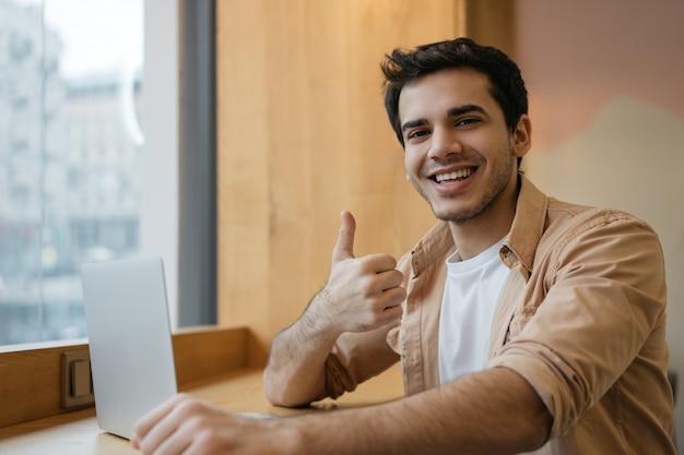 Uomo indiano che utilizza computer portatile, guardando corsi di formazione online, mostrando pollice in su, lavorando da casa
