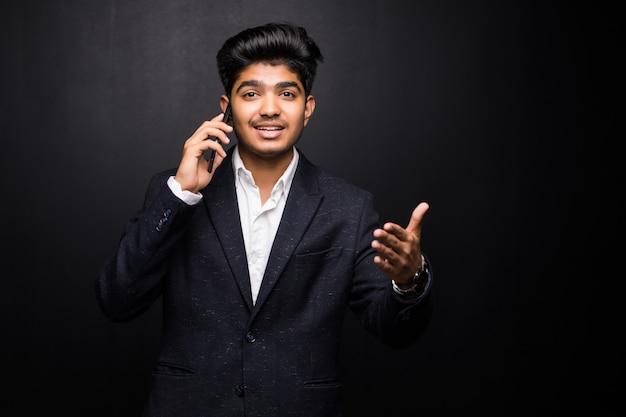 Uomo indiano di affari che parla sul telefono sulla parete nera