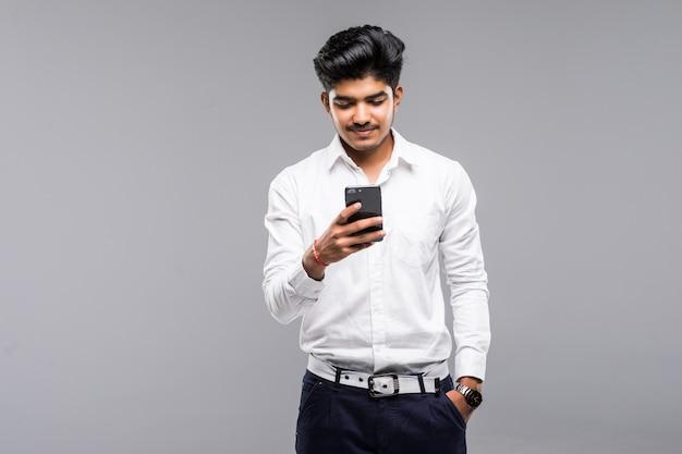 Uomo indiano di affari che per mezzo dello smartphone con la parete bianca