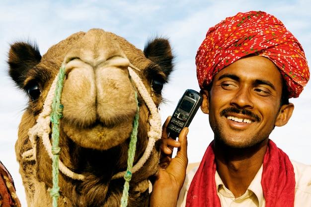 Uomo indiano e cammello al telefono, rajasthan, india.