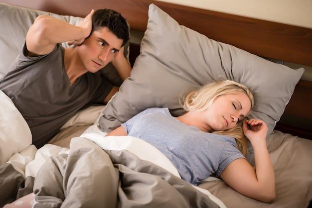 Uomo infastidito dal russare del suo compagno