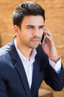 Uomo intelligente con un telefono in un orecchio