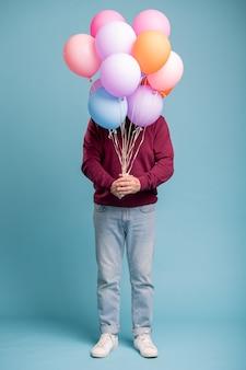 Uomo invecchiato casuale con il mazzo di palloncini colorati che fanno sorpresa di compleanno per qualcuno