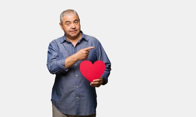 Uomo invecchiato centrale che celebra il giorno di biglietti di s. valentino che tiene qualcosa con la mano