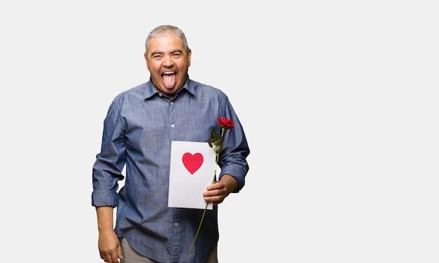 Uomo invecchiato centrale che celebra il giorno di biglietti di s. valentino funnny e lingua di mostra amichevole