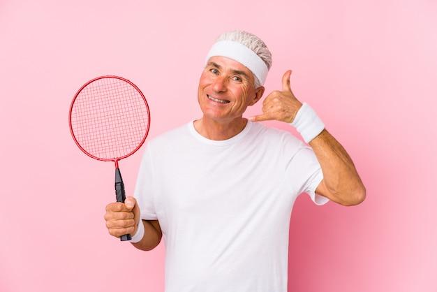 Uomo invecchiato centrale che gioca volano isolato mostrando un gesto di chiamata di telefono cellulare con le dita.