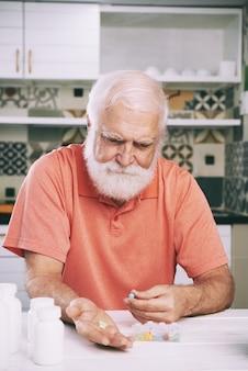 Uomo invecchiato che cattura le pillole