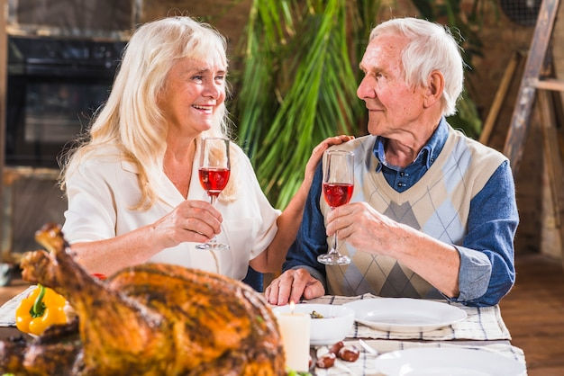 Uomo invecchiato e donna con gli occhiali al tavolo