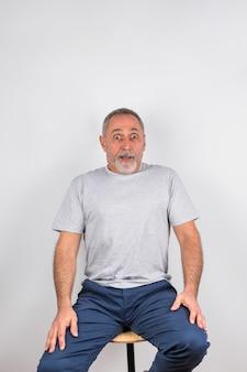 Uomo invecchiato stupito sulla sedia