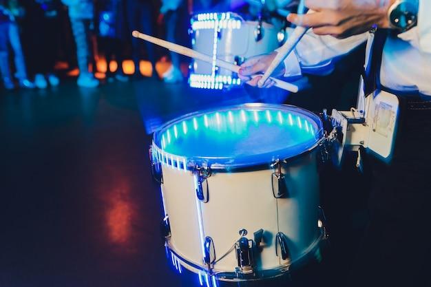 Uomo irriconoscibile che marcia mentre suona il tamburo sul tamburo.