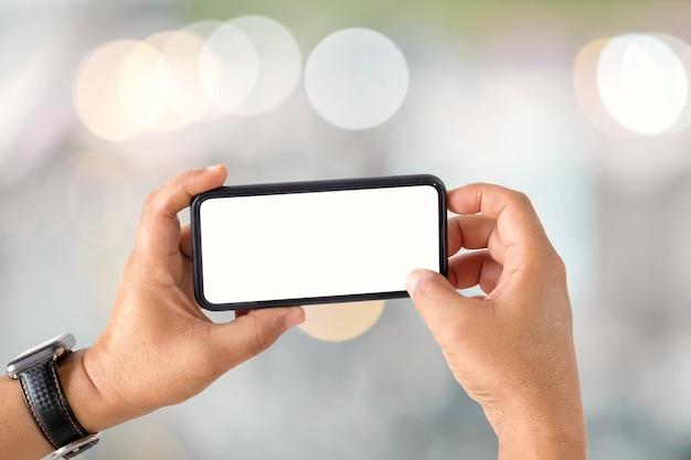 Uomo irriconoscibile che mostra un telefono cellulare dello schermo in bianco sopra fondo vago del bokeh