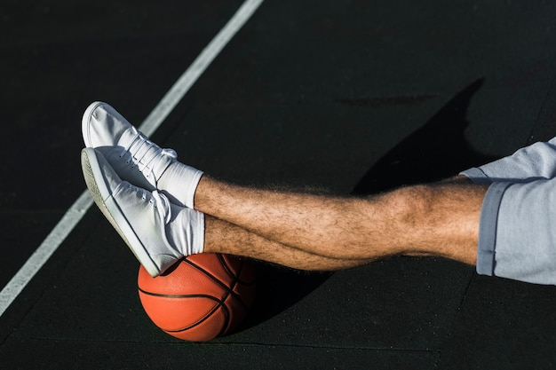 Uomo irriconoscibile che si distende sul campo da basket
