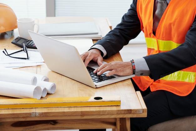 Uomo irriconoscibile in giubbotto di sicurezza al neon e tailleur seduto alla scrivania e usando il portatile