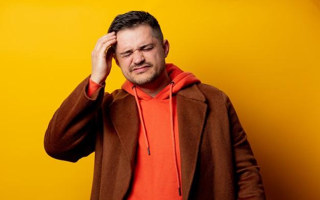 Uomo irritato in cappotto con mal di denti sulla parete gialla