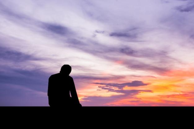 Uomo islamico che prega preghiera musulmana in tempo di twilight