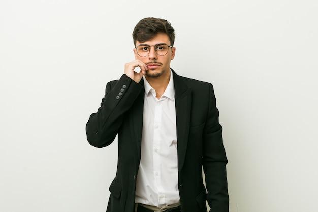 Uomo ispanico di giovani affari con le dita sulle labbra che tengono un segreto.