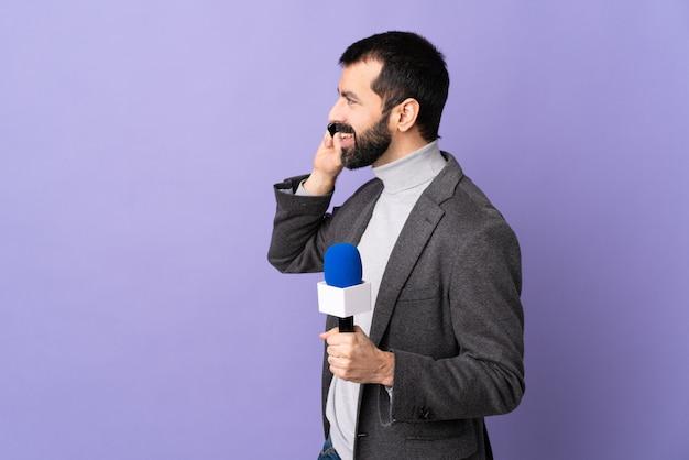 Uomo jounalist su sfondo viola isolato