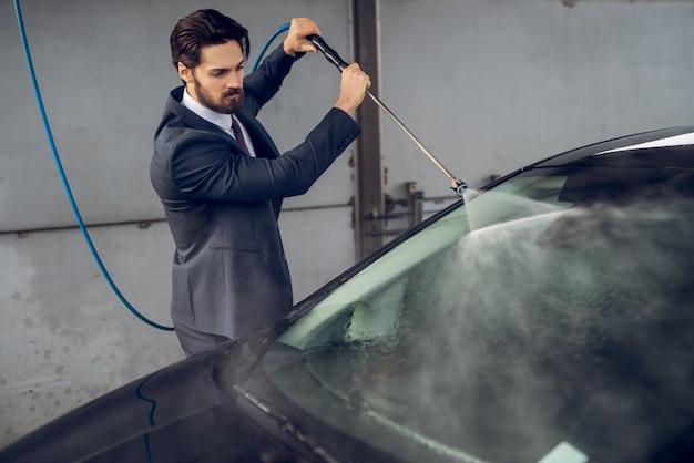 Uomo laborioso concentrato alla moda attraente barbuto in vestito che pulisce la sua automobile alla stazione di self service di lavaggio manuale dell'automobile.