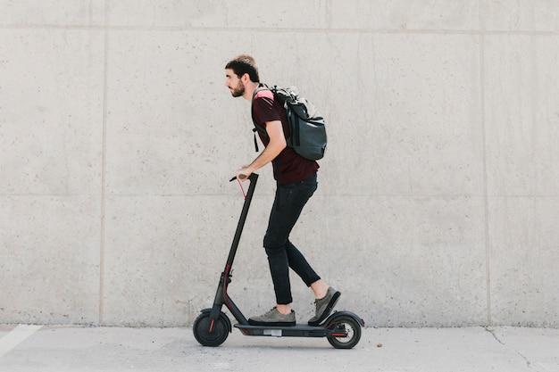 Uomo laterale che guida l'e-scooter