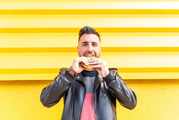 Uomo latino che mangia un hamburger all'aperto