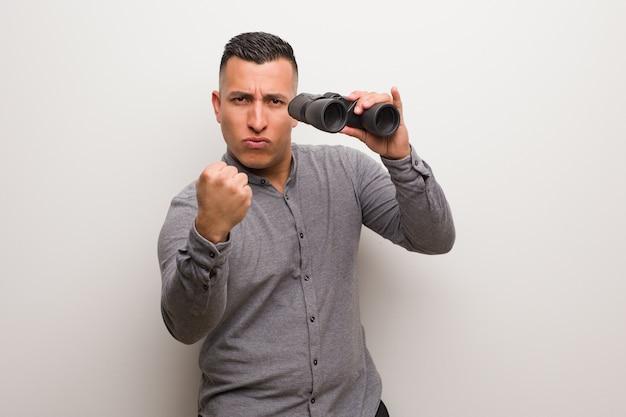 Uomo latino che mostra pugno in avanti, espressione arrabbiata