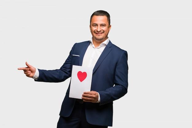 Uomo latino invecchiato centrale che celebra il giorno di biglietti di s. valentino che indica il lato con il dito