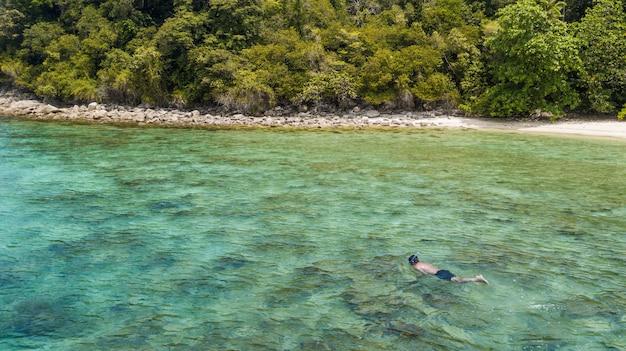 Uomo lo snorkeling da solo nel mare tropicale. perhentian island, malesia