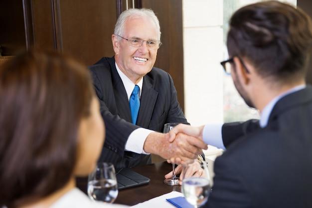 Uomo maggiore di affari che agita le mani con un altro giovane
