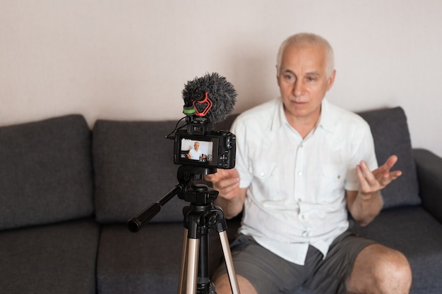 Uomo maggiore positivo che comunica in linea. vlogger anziano che trasmette in webcam