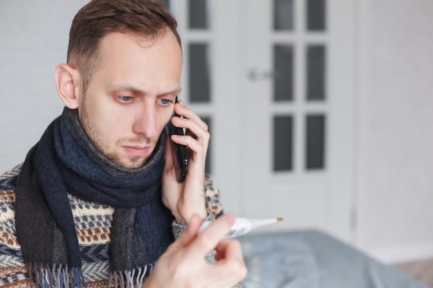 Uomo malato che chiama dal telefono che si siede a casa.