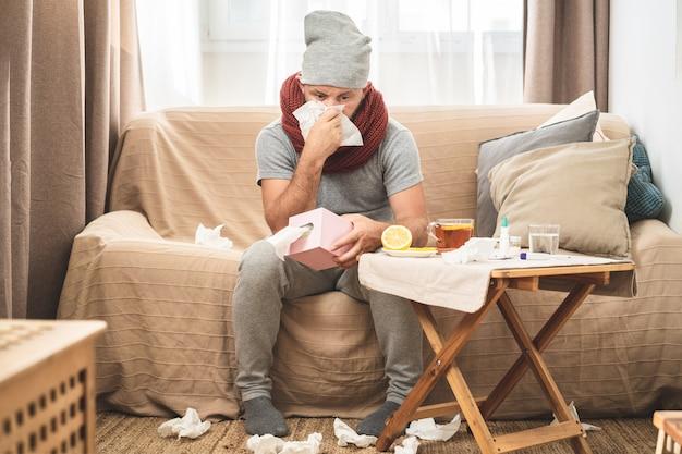 Uomo malato che indossa sciarpa e cappello grigio, soffiando il naso e starnutendo nel tessuto.