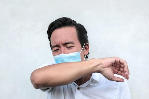 Uomo malato che indossa una maschera e tossisce al gomito