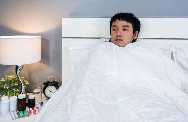 Uomo malato che sente freddo in coperta sul letto a casa