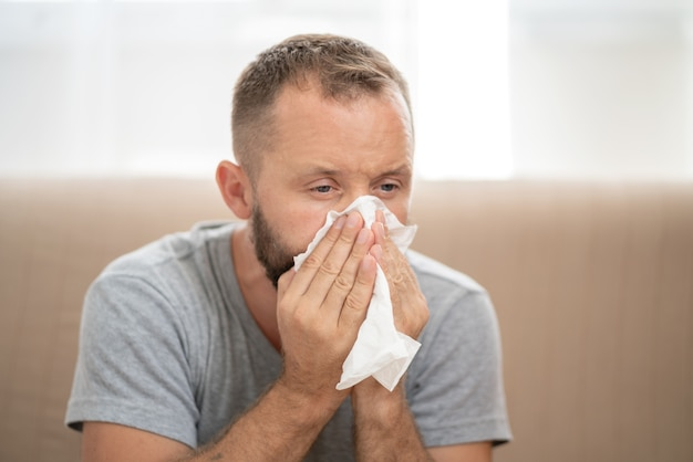 Uomo malato che soffia il naso e starnutisce nel tessuto