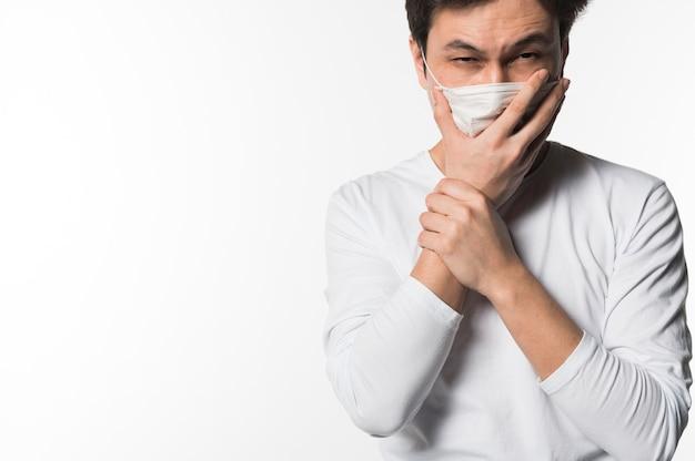 Uomo malato che tossisce nella mascherina medica