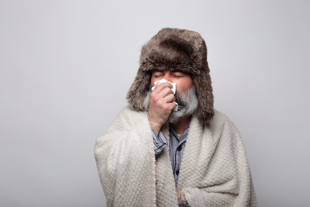 Uomo malato con cappello e coperta che soffia il moccio