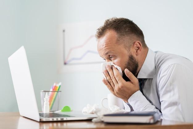 Uomo malato con fazzoletto che starnutisce soffiando naso mentre si lavora in ufficio, uomo d'affari catturato influenza fredda e stagionale.