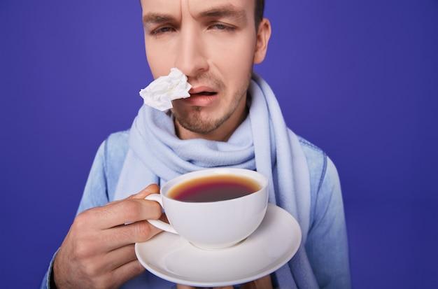 Uomo malato con tè anti-influenza nelle mani