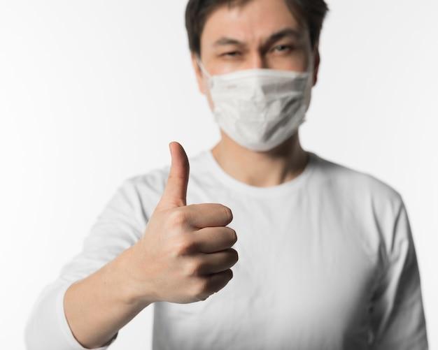 Uomo malato defocused con la mascherina medica che dà i pollici in su