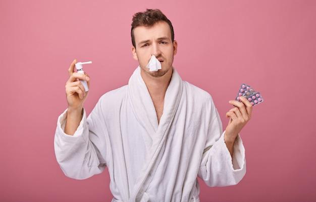 Uomo malato in camice bianco con un clistere una mano e pillole e inalatore in secondo