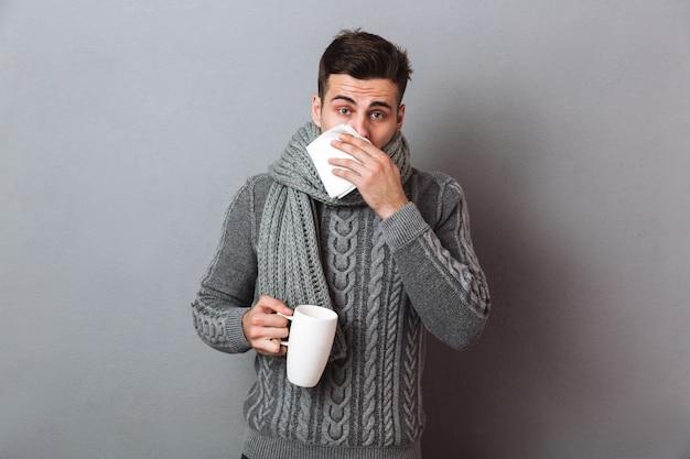 Uomo malato in maglione e sciarpa con naso che cola mentre si tiene la tazza di tè e alla ricerca