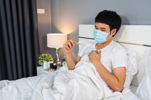Uomo malato nella maschera medica facendo uso del termometro per controllare la sua temperatura sul letto, concetto di pandemia di coronavirus.