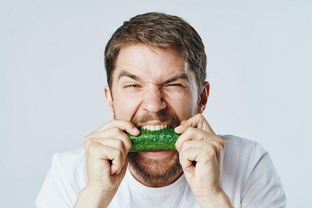 Uomo mangia cetriolo dieta close-up e sana
