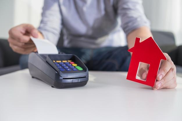 Uomo mantiene il terminale di pagamento per la casa